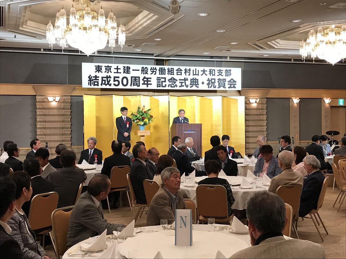 2018年5月20日(日)に立川市にあるホテル日航立川において「支部結成創立50周年式典」をおこないました。来賓には土建本・支部他、共闘・協力団体、各政党から33名、支部組合員85名の合計118名が出席しました。式典は、1部2部構成でおこなわれ、1部式典では渡辺委員長のあいさつに始まり、本部松丸委員長や三多摩労連坂ノ下副議長他のあいさつをいただき、元支部執行委員長の横谷荘壱さんによる「支部の歴史を振り返る」と題した記念講演をおこないました。/2部の祝賀会では、出席いただいた来賓に平野主任書記がマイクを持ってあいさつをいただきにまわりました。また、余興には、バンド演奏をバックに女性の会や歴代の役員、本部松丸委員長に歌を歌っていただき、全員での合唱をしました。最後は、今期より書記長になった藤田さんより60年、70年に向けて、そして春の拡大達成に向け、ガンバローとのあいさつで締めくくり閉会となりました。/